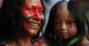 14jun2012---mulher-de-etnia-indigena-com-crianca-no-colo-sorri-durante-a-cerimonia-oficial-de-abertura-dos-jogos-verdes-na-aldeia-kari-oca-durante-a-rio20-1339721412822_956x500